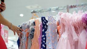 Il primo piano, mani femminili ha selezionato molti ganci con le attrezzature selezione ed acquisto dei vestiti nel deposito Acqu video d archivio