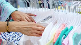Il primo piano, mani femminili ha selezionato molti ganci con le attrezzature selezione ed acquisto dei vestiti nel deposito Acqu archivi video
