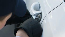 Il primo piano, mani gloved apre meccanicamente la serratura di porta dei car's immagini stock