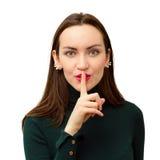 Il primo piano moderno e bello della ragazza mette un dito alle sue labbra nel segno di silenzio fotografie stock