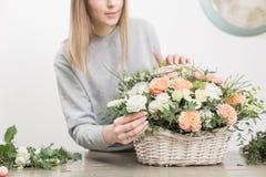 Il primo piano passa il gruppo di lavoro femminile di Floral del fiorista - donna che rende ad una bella composizione nel fiore u fotografia stock