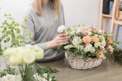 Il primo piano passa il gruppo di lavoro femminile di Floral del fiorista - donna che rende ad una bella composizione nel fiore u immagine stock