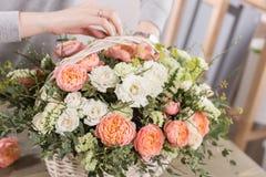 Il primo piano passa il gruppo di lavoro femminile di Floral del fiorista - donna che rende ad una bella composizione nel fiore u fotografie stock libere da diritti