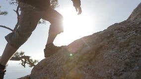 Il primo piano seguente dinamico ha sparato di un uomo che scala una montagna Dettaglio degli stivali di alpinismo ed uomo avvent video d archivio