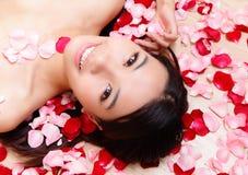 Il primo piano sorridente della ragazza asiatica di bellezza con è aumentato Immagine Stock