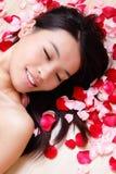 Il primo piano sorridente della ragazza asiatica di bellezza con è aumentato Fotografie Stock