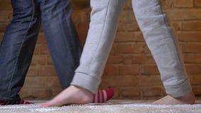 Il primo piano sparato di ballare femminile e maschio attivamente su un tappeto simile a pelliccia sopra bricken il fondo della p video d archivio