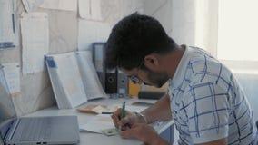 Il primo piano, studente indiano fa uno schizzo su un autoadesivo, prepara uno strato di imbroglione per un esame di medicin stock footage