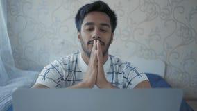 Il primo piano, studente indiano Sitting ad un computer portatile decolla i vetri e sfrega il suo fronte con le mani archivi video