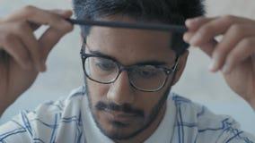 Il primo piano, studente indiano in vetri gira in mani della matita e Pensively guarda prima di se stesso, prepara per gli esami archivi video