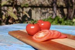 Il primo piano succoso della vite rossa matura ha maturato i pomodori affettati ed interi immagine stock libera da diritti