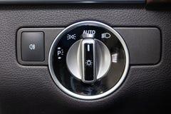 Il primo piano sui bottoni di controllo del commutatore del faro ed automatici regolano il cruscotto del livello in automobile ne fotografia stock