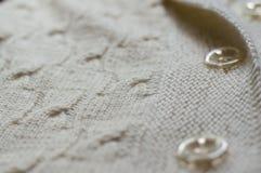 Il primo piano sul dettaglio bianco dell'artigianato tessuto tricotta il maglione o cadigan Fotografie Stock