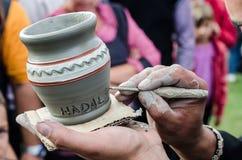 Il primo piano sull'artista passa la personalizzazione della brocca dell'argilla scrivendo il nome di una persona. Fotografia Stock