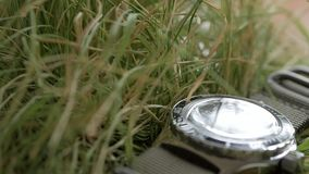 Il primo piano sull'erba verde si trova un orologio d'immersione con enfasi sul movimento dell'usato rosso sul nero video d archivio