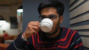 Il primo piano, tipo indiano beve il caffè al caffè archivi video