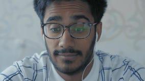 Il primo piano, il tipo indiano in vetri e le cuffie attentamente esamina le notizie di radiodiffusione su un computer portatile video d archivio