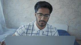 Il primo piano, tipo indiano in vetri esamina pensively il monitor del computer portatile con la matita a disposizione archivi video