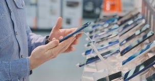 Il primo piano un uomo sceglie due telefoni sul contatore da uno smartphone più potente e più moderno per l'affare acquisto stock footage