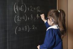 Il primo selezionatore italiano della ragazza della scuola elementare risolve la matematica Fotografia Stock