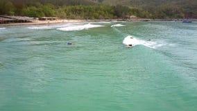 Il principiante distante del surfista aumenta sul surf sull'onda di oceano stock footage