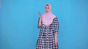 Il problema è l'odore di sudore, una giovane donna musulmana nel hijab che esamina la macchina fotografica archivi video