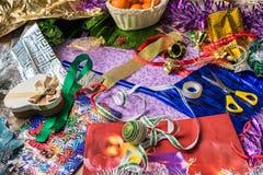 Il processo dei regali di festa di Natale dell'imballaggio Carta da imballaggio, nastro, decorazioni di Natale Vista da sopra Fotografia Stock