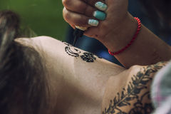 Il processo del fuoco di mendi del disegno sul tatuaggio Immagine Stock