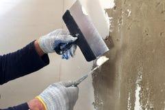 Il processo del mastice del muro di cemento due spatole Immagine Stock