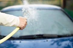 Il processo delle automobili di lavaggio con un tubo flessibile con acqua Fotografie Stock