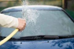 Il processo delle automobili di lavaggio con un tubo flessibile con acqua Immagine Stock Libera da Diritti