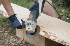 Il processo di abrasione della buccia della plancia di legno da desidera ardentemente il soffitto della casa di ceppo Fotografie Stock
