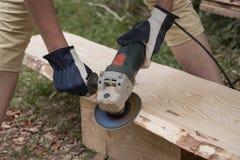 Il processo di abrasione della buccia della plancia di legno da desidera ardentemente il soffitto della casa di ceppo Fotografia Stock