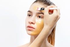 Il processo di applicazione della maschera cosmetica gialla con una spazzola sul fronte di giovane ragazza castana fotografia stock libera da diritti