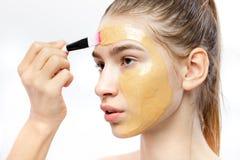 Il processo di applicazione della maschera cosmetica gialla con una spazzola sul fronte di giovane ragazza castana fotografia stock