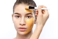 Il processo di applicazione della maschera cosmetica gialla con una spazzola sul fronte di giovane ragazza castana fotografie stock libere da diritti