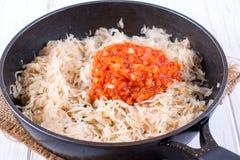 Il processo di cottura del cavolo stufato con le carote e le spezie in una padella Fotografia Stock