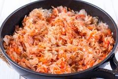 Il processo di cottura del cavolo stufato con le carote e le spezie in una padella Fotografie Stock Libere da Diritti