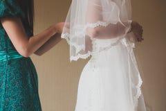 Il processo di installazione del vestito della sposa Immagini Stock Libere da Diritti