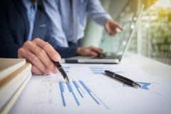 Il processo di lavoro di squadra, uomini d'affari passa indicare al computer portatile ed al documento immagini stock libere da diritti