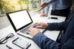 Il processo di lavoro di squadra, uomini d'affari passa indicare al computer portatile ed al documento immagini stock