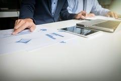 Il processo di lavoro di squadra, uomini d'affari passa indicare al documento durante immagine stock