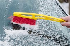 Il processo di liberare il parabrezza dell'automobile dalla neve con una spazzola rossa e gialla fotografia stock libera da diritti