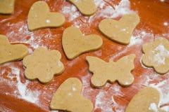 Il processo di produrre i biscotti dello zenzero sotto forma di cuore, di fiore e di farfalla, pan di zenzero fotografie stock
