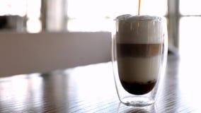 Il processo di produrre il latte del caffè in un vetro stelean su una tavola archivi video