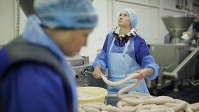 Il processo di produrre le salsiccie in una pianta di imballaggio della carne I lavoratori in uniforme producono la salsiccia video d archivio
