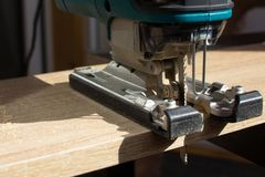 Il processo di segare un bordo di legno con un puzzle dal tuttofare fotografie stock libere da diritti