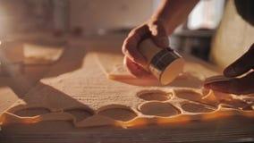 Il processo di taglio della pasta nei piccoli cerchi con un dispositivo speciale stock footage