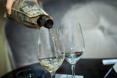 Il processo di versamento del vino bianco assaggio cieco Immagine Stock