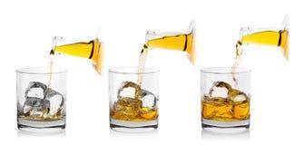 Il processo di versamento del whiskey dalla bottiglia in vetro Immagini Stock Libere da Diritti